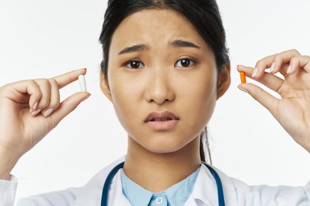 Médecin tenant différentes pilules avec indécision