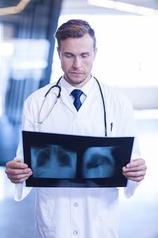 Médecin tenant et examinant une radiographie à l'hôpital
