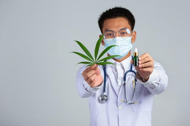Médecin tenant une feuille de cannabis et une bouteille d'huile de cannabis sur un mur blanc.