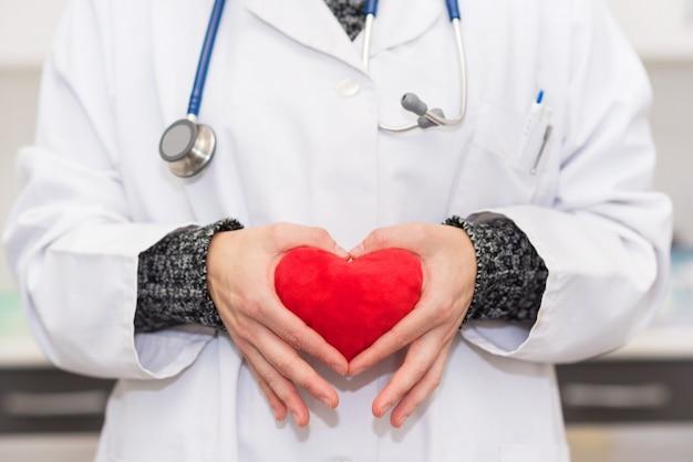 Médecin tenant une forme de coeur rouge
