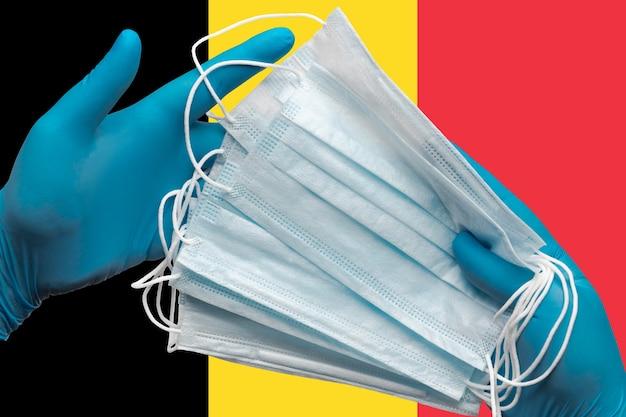 Médecin tenant des masques médicaux dans les mains des gants bleus sur fond drapeau national de la belgique. concept de quarantaine de coronavirus, grippe, épidémie de pandémie, hygiène. bandage chirurgical antibactérien pour le visage.