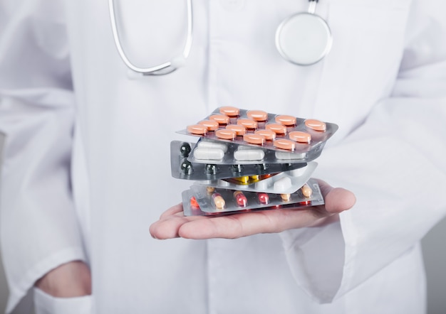 Médecin tenant la pile de différentes pilules, antibiotiques et comprimés de traitement de virus sur le mur gris de l'hôpital. macro