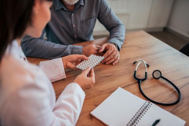 Médecin tenant des pilules, parler à un patient âgé, gros plan.