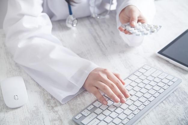 Médecin tenant des pilules et en tapant au clavier. médicament