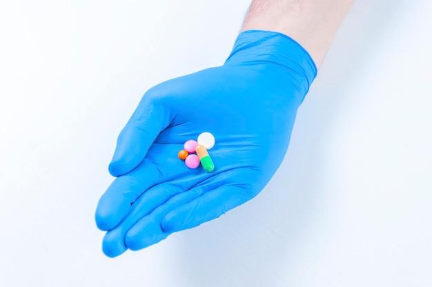 Le médecin tend des pilules sur un gant bleu. concept médical.