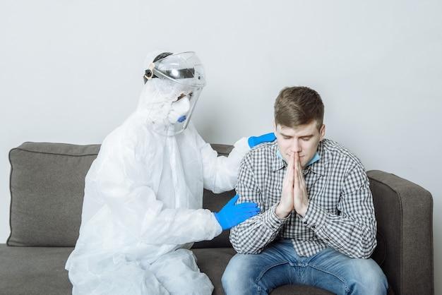 Un médecin en tenue de protection avec un masque et des gants, remonte le moral d'un patient atteint de coronavirus lors d'une épidémie de virus et d'une pandémie