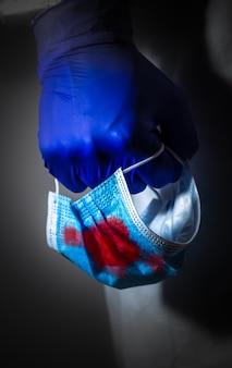 Médecin en tenue de protection médicale et gants, tenant un masque médical dans le sang dans sa main. la fin de la pandémie de virus. mers de protection par épidémie de virus. coronavirus (covid-19). concept de soins de santé.