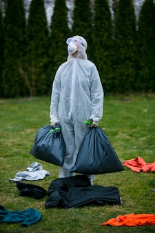 Un médecin en tenue de protection recueille les objets laissés par les personnes infectées dans des sacs