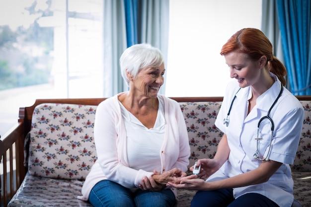 Médecin testant le niveau de glucose d'un patient à l'aide d'un glucomètre numérique