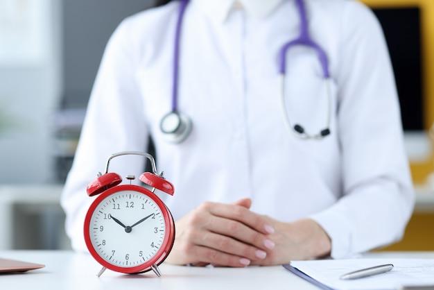 Médecin thérapeute assis au bureau en face de gros plan de réveil rouge. horaire des médecins