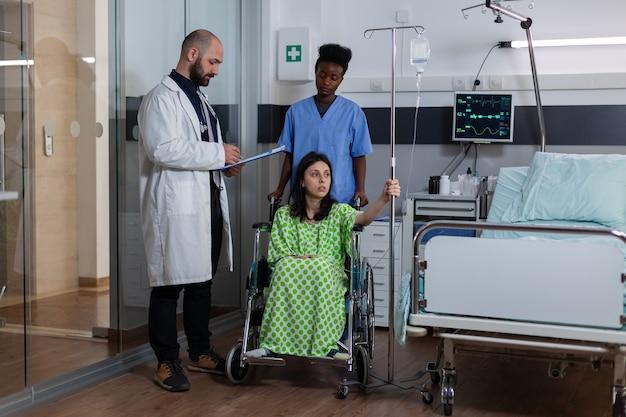Médecin thérapeute écrivant le rétablissement de la maladie sur le presse-papiers dans la salle d'hôpital