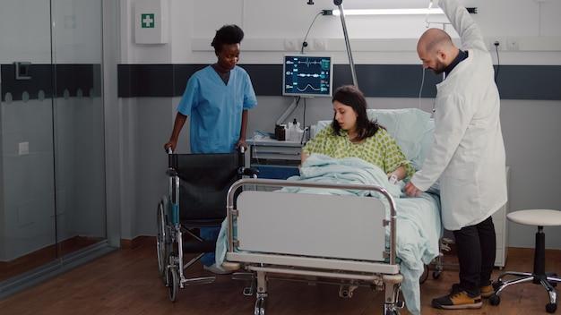 Médecin thérapeute surveillant le pouls cardiaque pendant la récupération médicale dans la salle d'hôpital