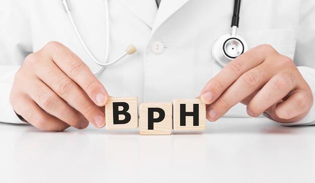 Le médecin tient des cubes en bois dans ses mains avec du texte hbp