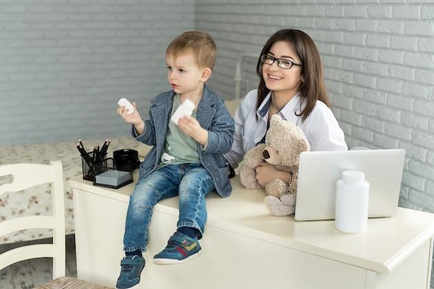 Le médecin tient dans les bras le flacon de pilules et l'offre à l'enfant visiteur
