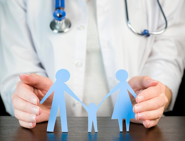 Le médecin tient une figure de famille. concept de protection de la famille.