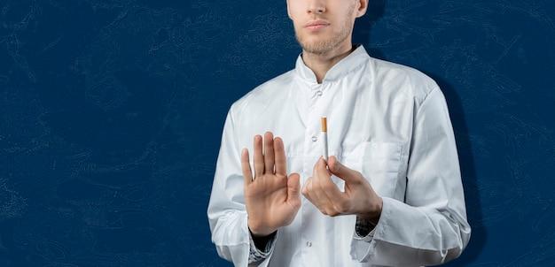 Un médecin tient et freine la cigarette, arrête et arrête de fumer