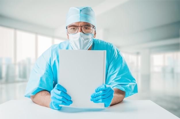 Le médecin tient un livre de référence blanc devant lui