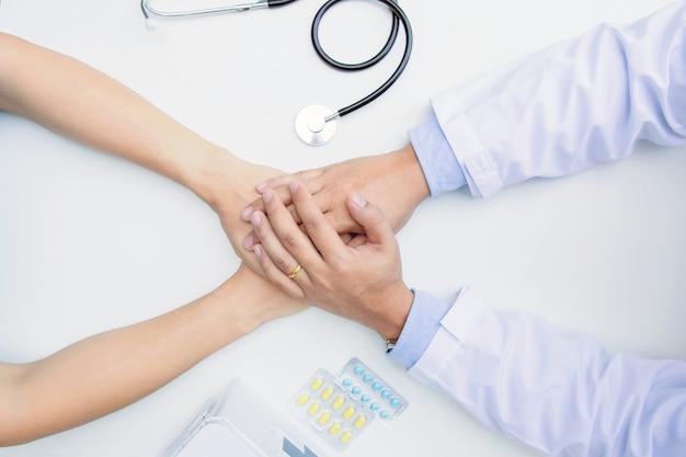 Le médecin tient les mains du patient. il lui donne de l'espoir et le soutient