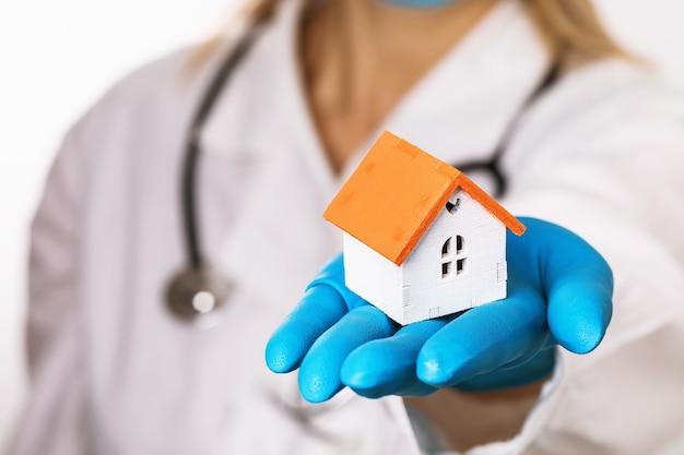 Le médecin tient une maison de jouet sur le médecin à domicile de concept de paume