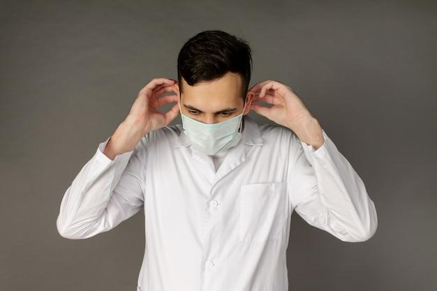 Le médecin tient et met un masque médical pour se protéger du coronavirus