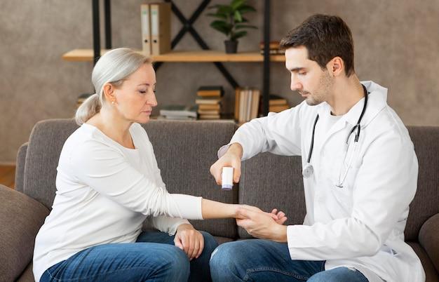 Médecin de tir moyen à l'aide d'un thermomètre