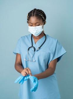 Médecin de tir moyen mettant des gants