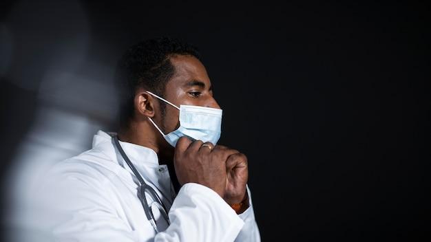 Médecin de tir moyen portant un masque facial