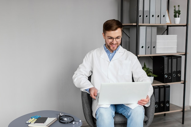 Médecin de tir moyen tenant un ordinateur portable
