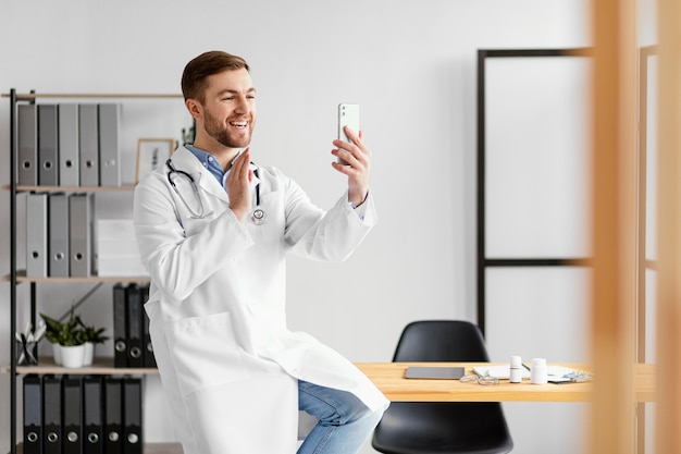Médecin de tir moyen tenant un smartphone