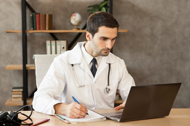 Médecin de tir moyen travaillant sur ordinateur portable