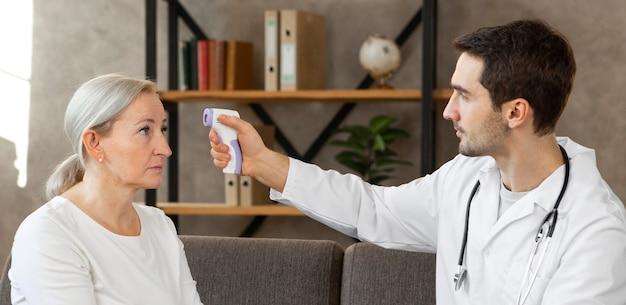 Médecin de tir moyen vérifiant la température du patient