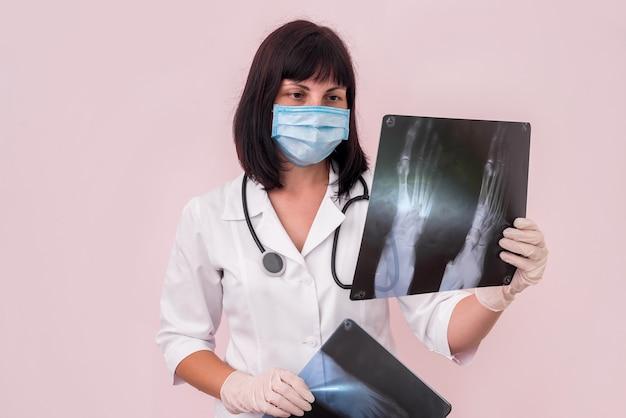 Médecin traumatologue avec radiographie du pied d'un patient