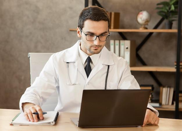 Médecin travaillant sur un ordinateur portable coup moyen