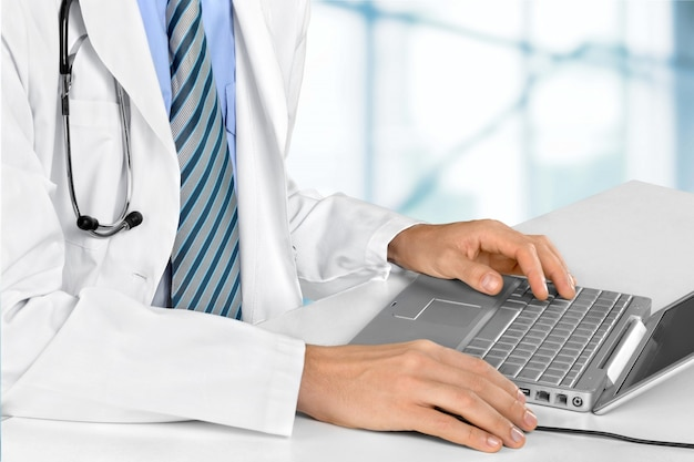 Médecin travaillant sur un ordinateur portable se bouchent