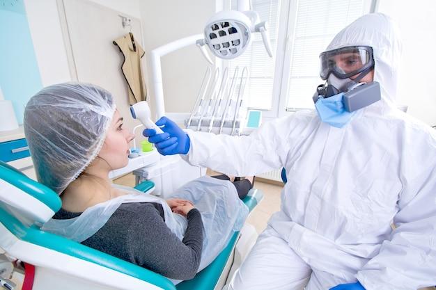 Médecin en uniforme de protection et masque vérifiant la température de la jeune patiente.
