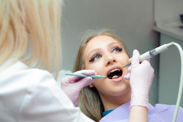 Médecin en uniforme vérifiant les dents de la patiente dans les soins dentaires