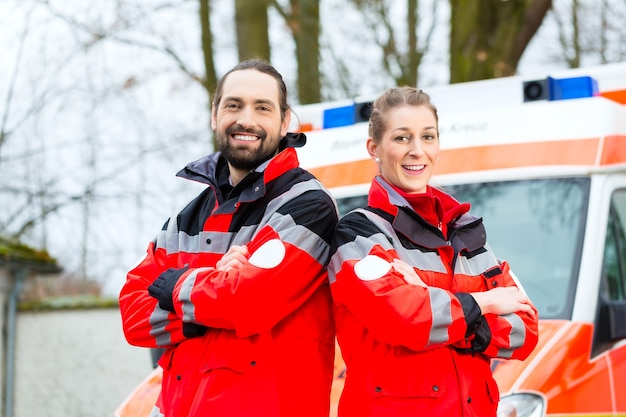 Médecin d'urgence et infirmière debout devant la voiture d'ambulance