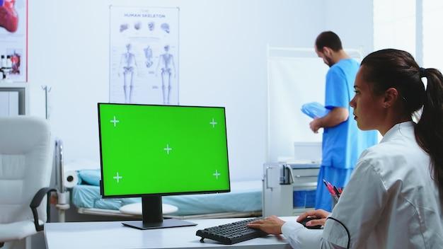 Médecin utilisant un ordinateur avec écran vert dans l'armoire de l'hôpital et assistant en arrière-plan. médecin en blouse blanche travaillant sur moniteur avec clé chroma dans l'armoire de la clinique pour vérifier le diagnostic du patient.