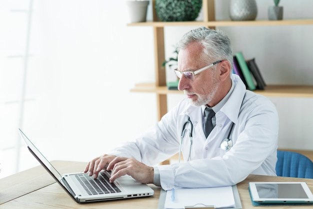 Médecin utilisant un ordinateur portable au bureau