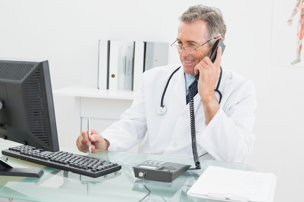 Médecin utilisant un ordinateur et un téléphone au bureau