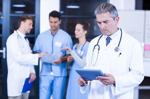 Médecin utilisant une tablette et collègues discutant