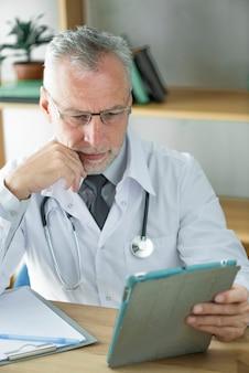 Médecin utilisant une tablette et pensant