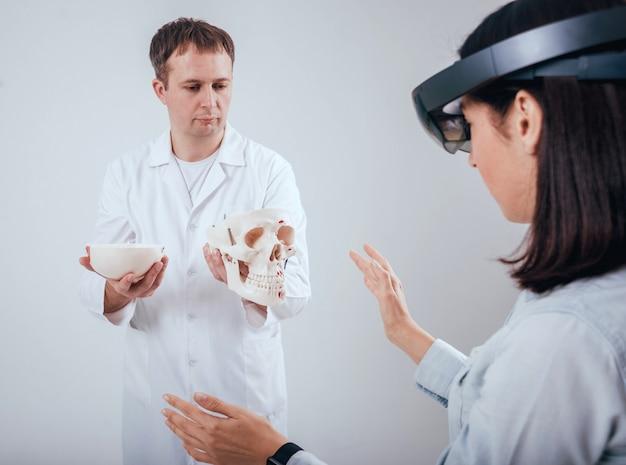 Un médecin utilise des lunettes de réalité augmentée et un squelette humain pour enseigner à un étudiant