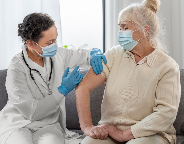 Médecin vaccinant une femme âgée