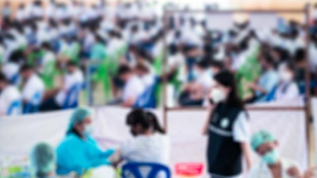 Le médecin vaccine les étudiants en uniforme pour prévenir le coronavirus ou le covid-19. flou flou pour l'arrière-plan