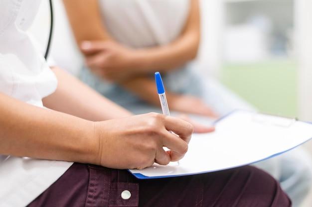 Médecin vérifiant le formulaire médical avec le patient