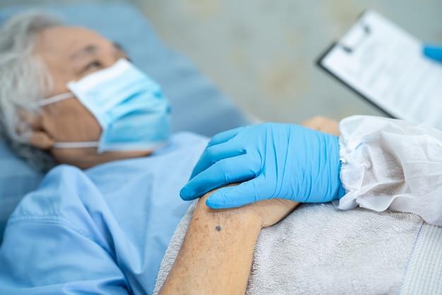 Médecin vérifiant une patiente asiatique âgée portant un costume de ppe pour protéger l'infection covid coronavirus