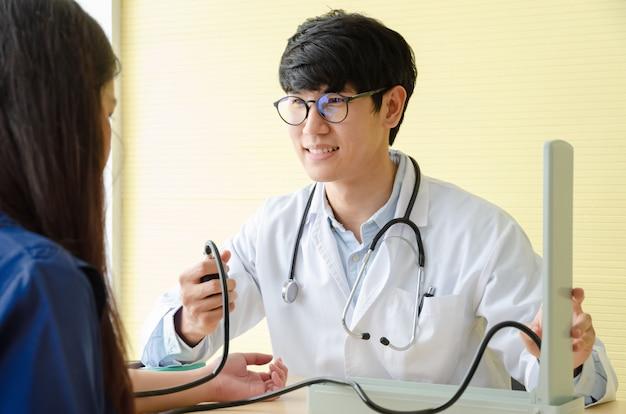 Médecin vérifiant la pression artérielle patiente en cabinet médical