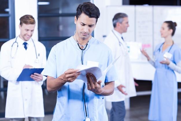 Médecin vérifiant le rapport médical pendant que ses collègues discutent