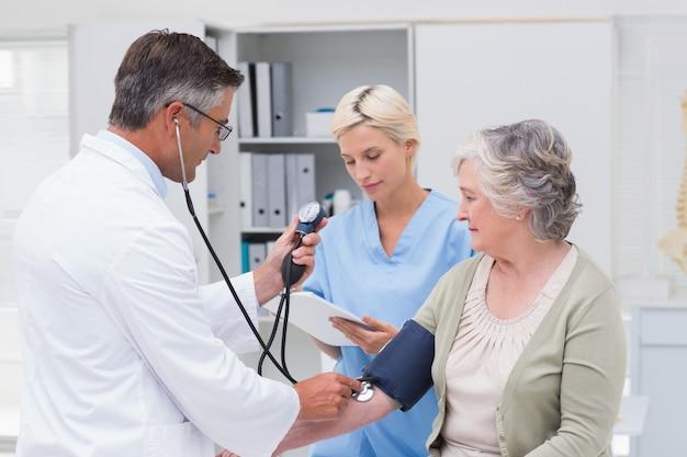 Médecin vérifiant la tension artérielle des patients pendant que l'infirmière le notait